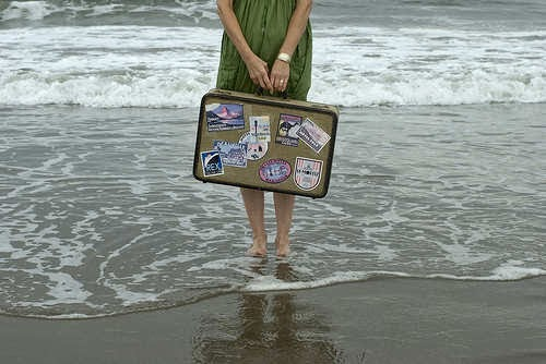 girl-travelling-solo-standing-on-beach-with-suitcase